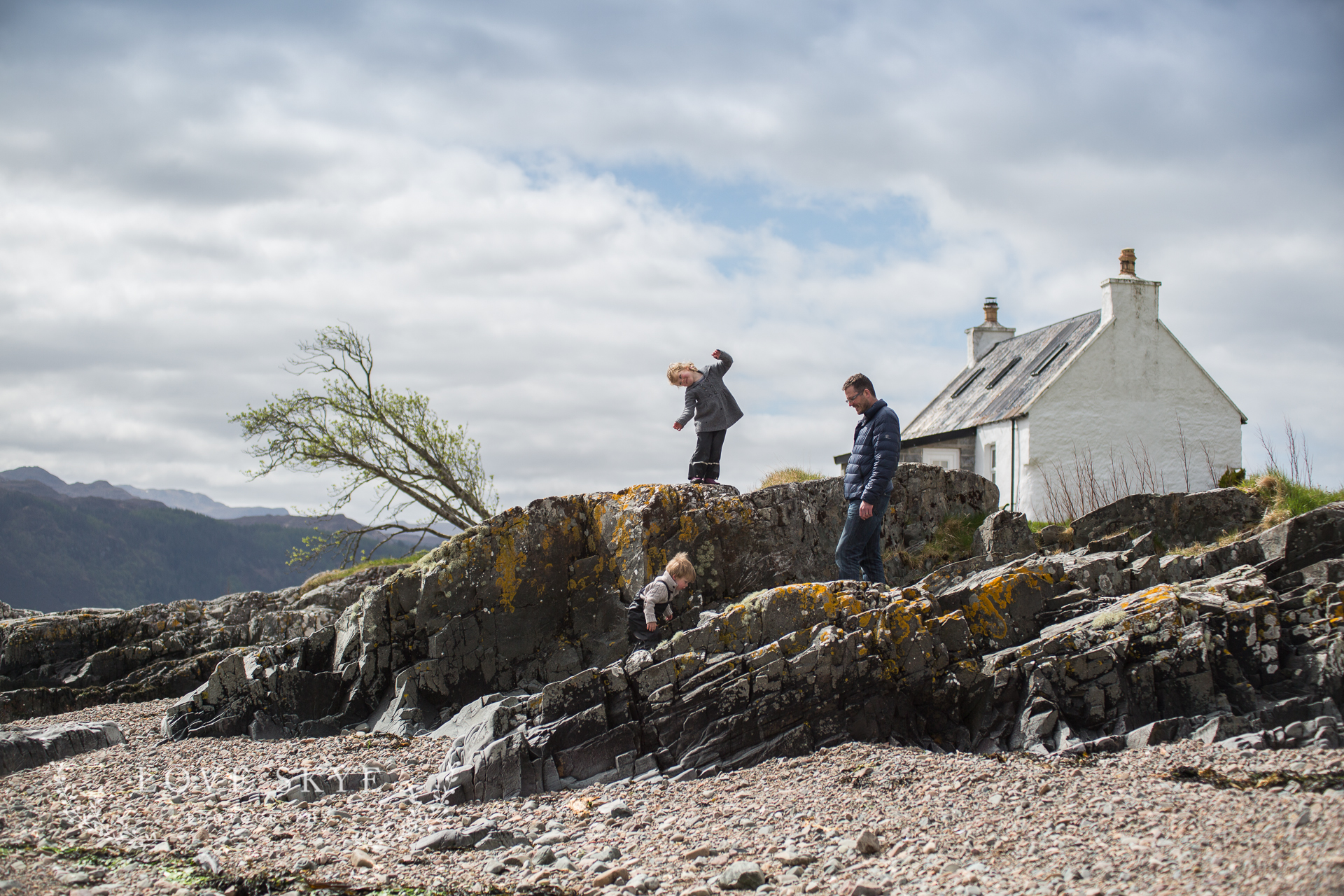 Isle of Skye family photographer family on beach with small white house in background