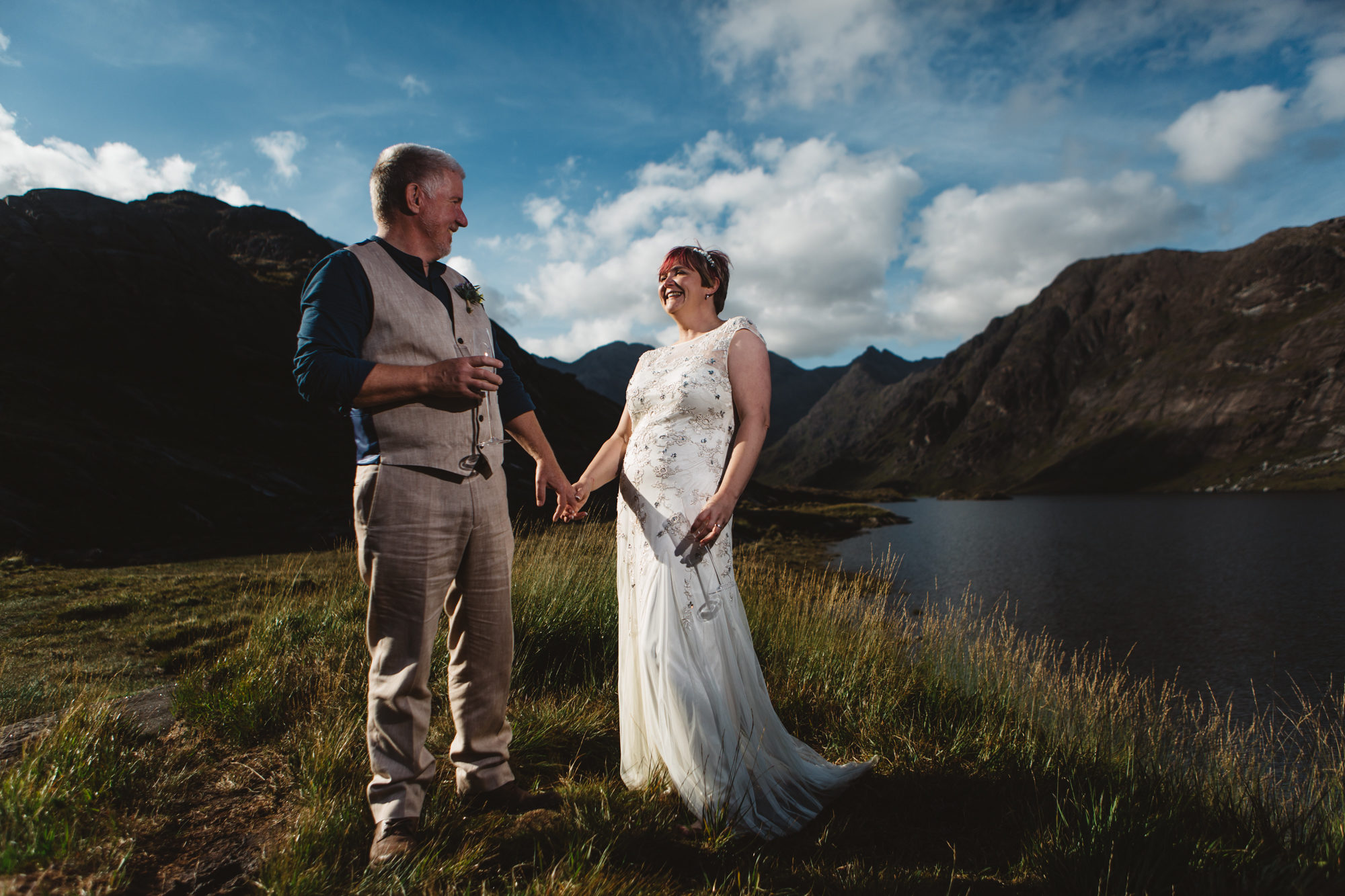 Bride and groom laughing and holding hands at Loch Coruisk