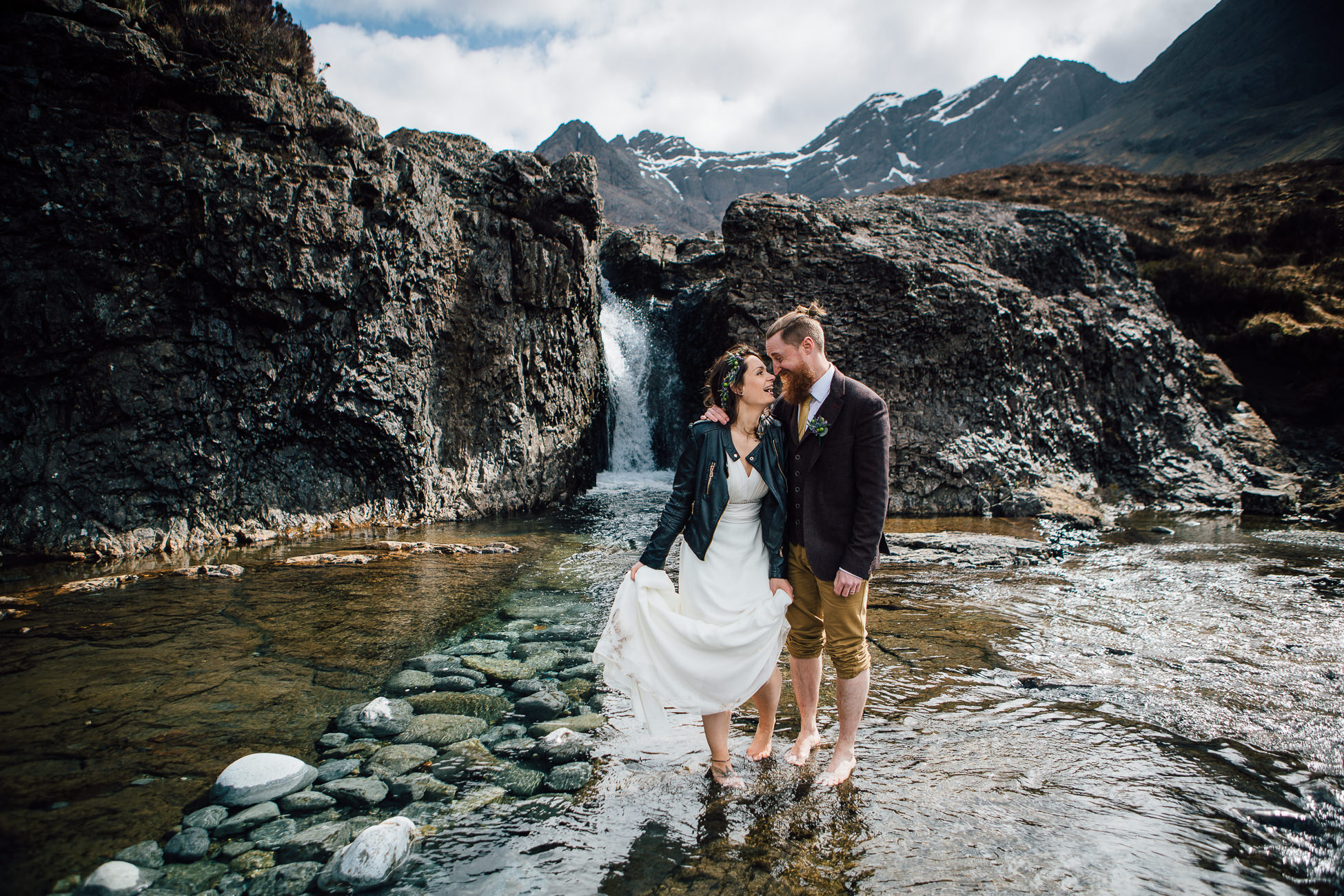 Bride and groom standing in water at Fairy Pools Isle of Skye snow on mountains
