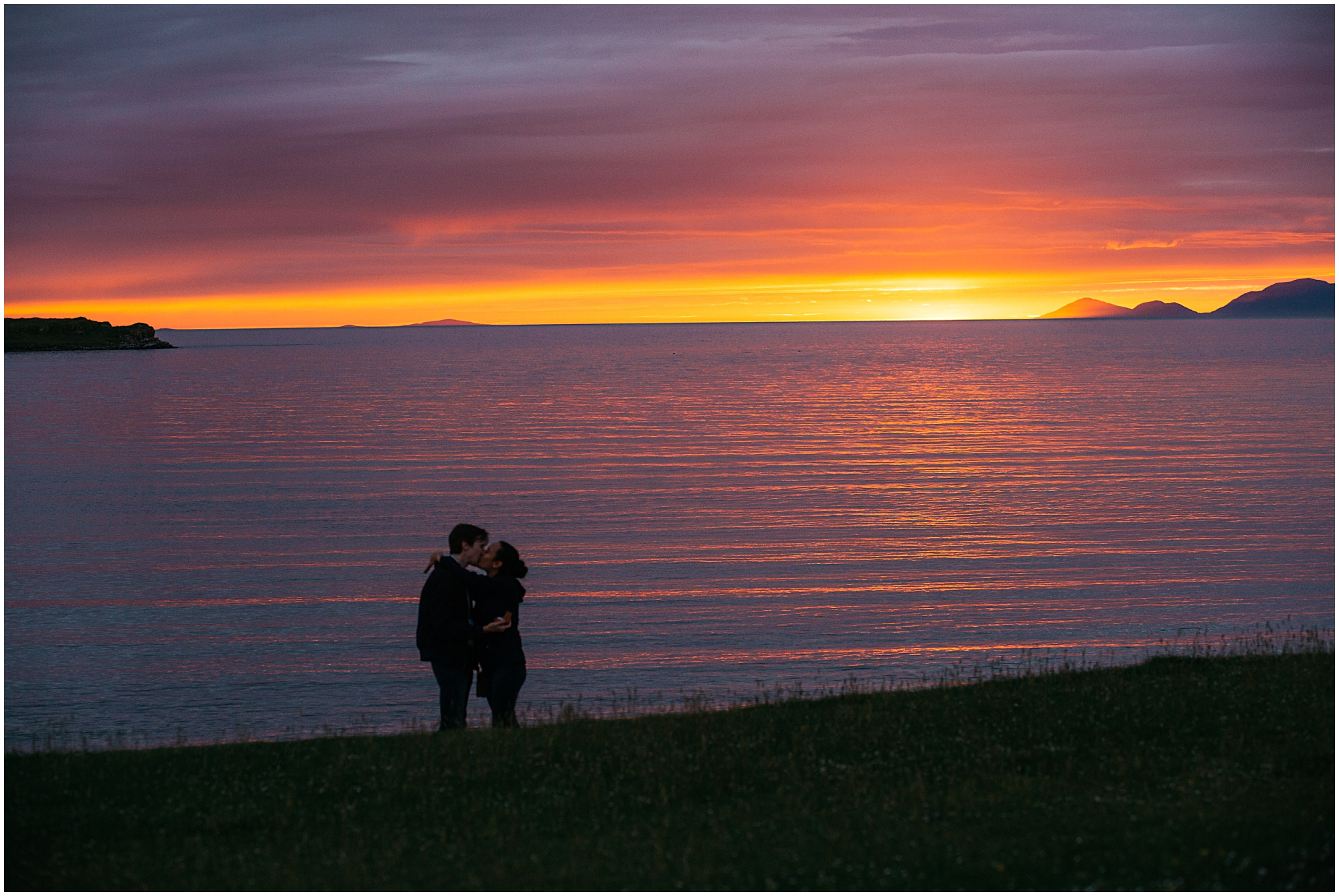 Silhoutted couple embrace against sunset lit sea and sky
