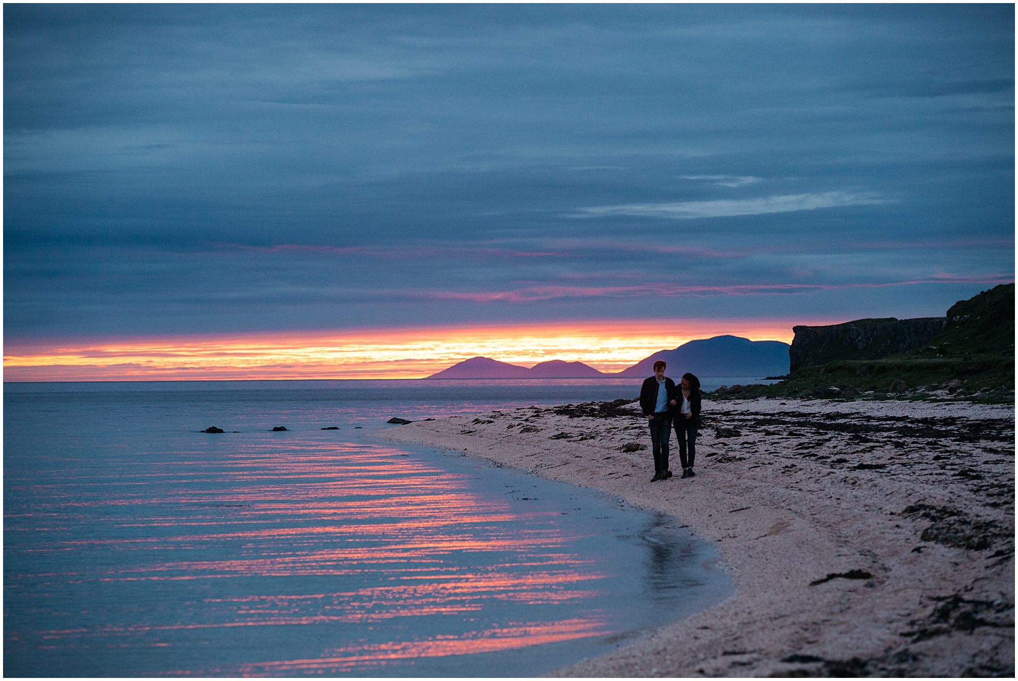 Couple walk hand in hand on Coral beach Isle of Skye at sunset
