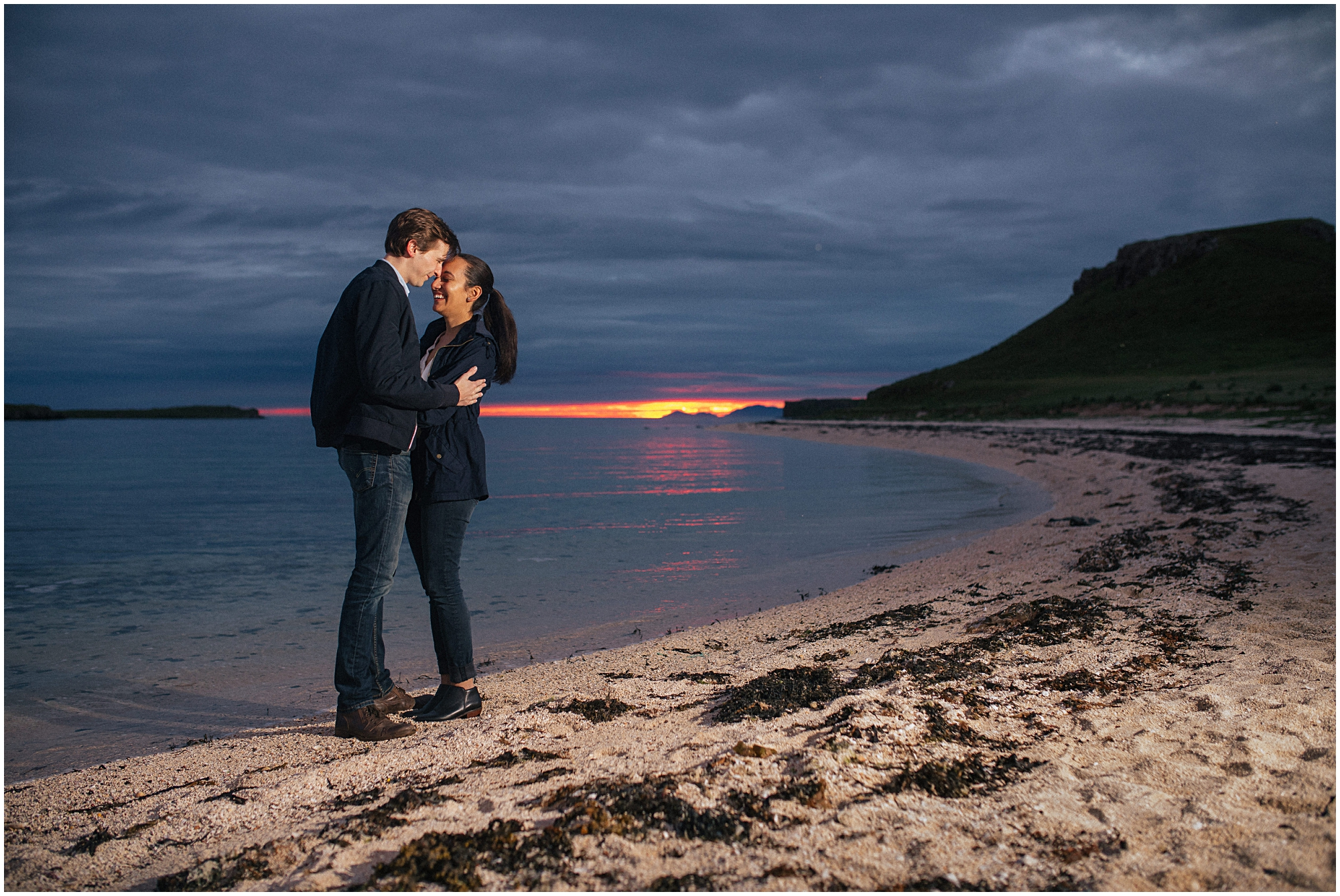 Couple hug on watersedge of Coral Beach, Skye at sunset