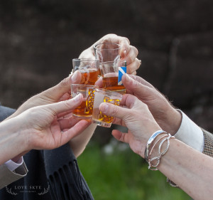 shot glasses of whisky held for a toast
