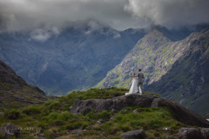 Bride and groom dance atop hillock with Cuillin in background Isle of Skye