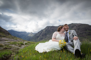 bride and groom sit on grass and flowers at Loch Coruisk bride leans head into groom. smiling cuillin in background