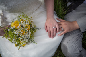 Wedding rings bride and groom hold hands close up with yellow daisy bouquet
