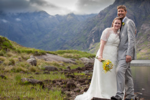 Bride and groom stand at Loch Coruisk Isle of Skye