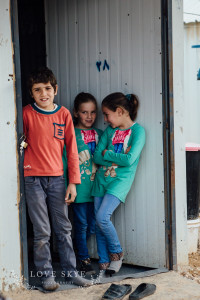 Children giggle in doorway of shelter at Azraq camp