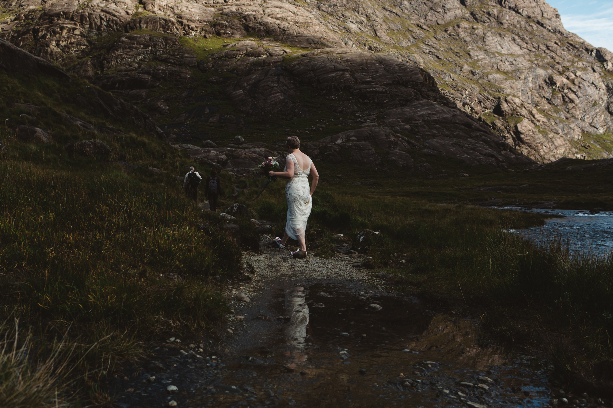 Bride and groom walk to ceremony reflected in water loch coruisk