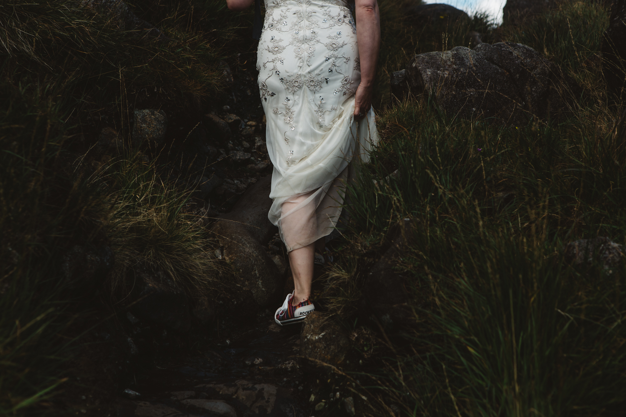 Bride and groom walk to ceremony among mountains loch coruisk