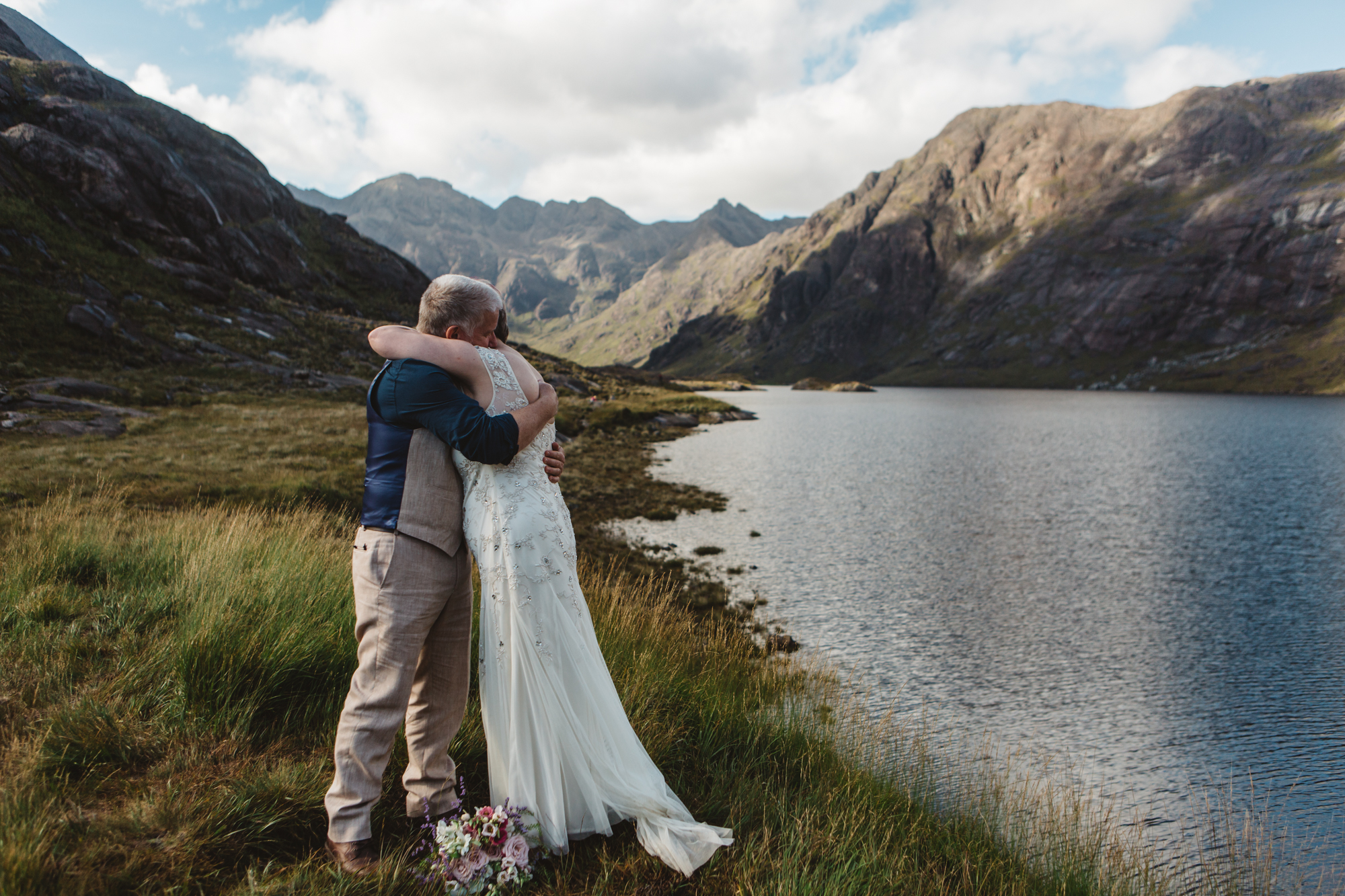 Bride and groom embrace during wedding ceremony loch coruisk
