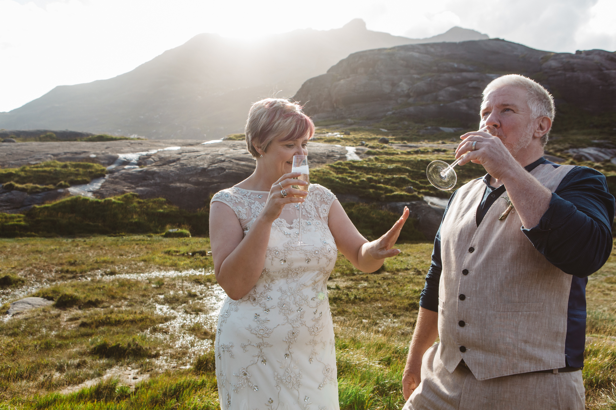 Bride sips champagne and looks at wedding ring Loch Coruisk