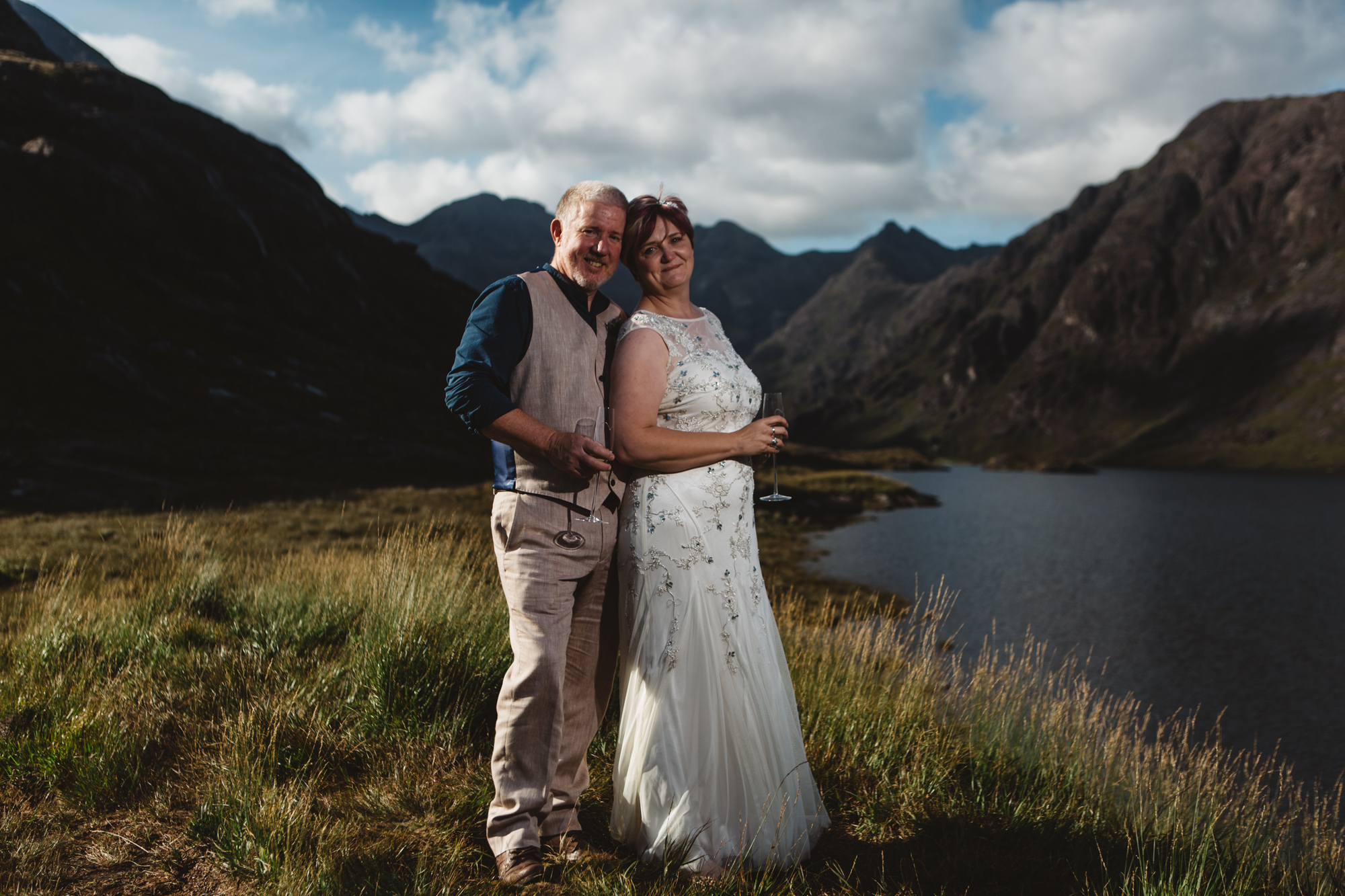 Bride and groom cuddling for photographs at Loch Coruisk