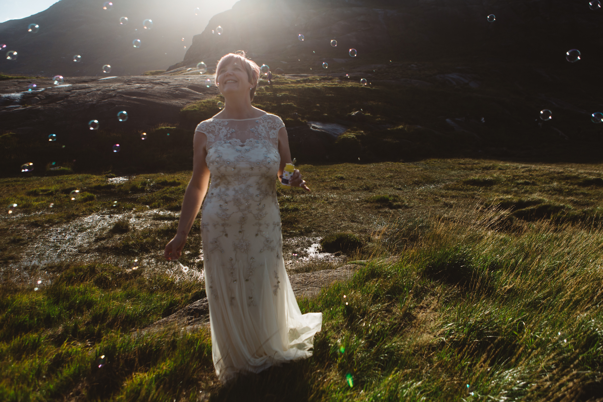 Backlit bride surrounded by bubbles at Loch Coruisk