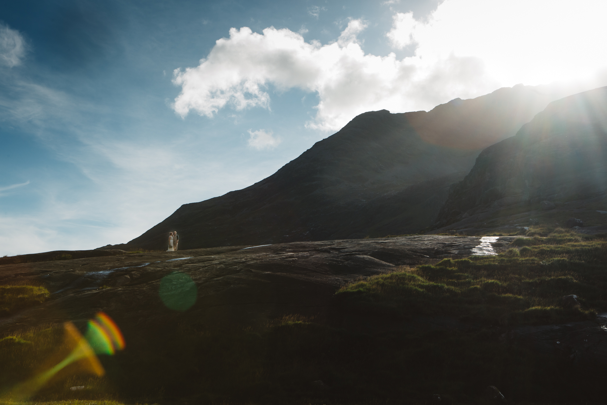 Tiny bride and groom on rock slabs with sun flare at Loch Coruisk