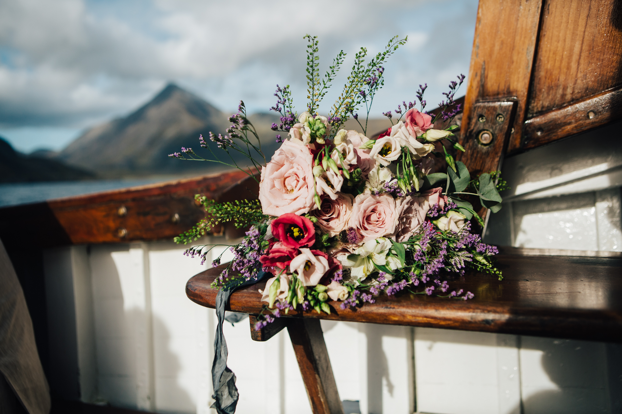 wedding bouquet of pink and wild flowers on wooden seating of Misty Isle boat