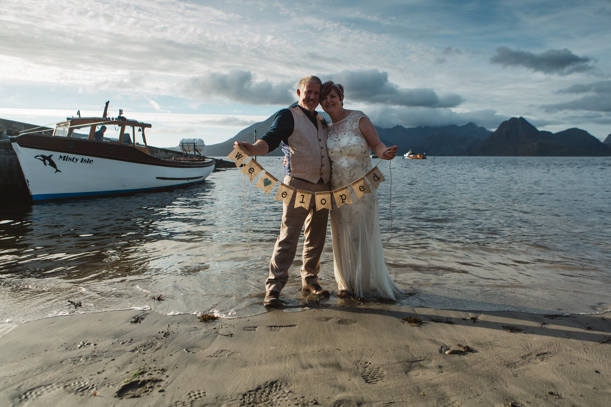 Bride and groom on beach at Elgol Misty Isle and Cuillin in background holding we eloped sign