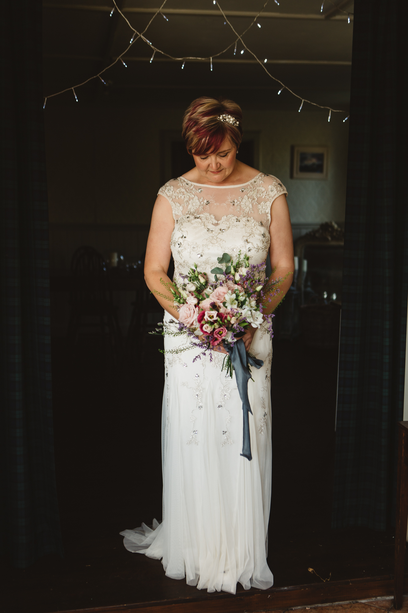 Beaming bride in wedding dress short pink hair looking down holding bouquet