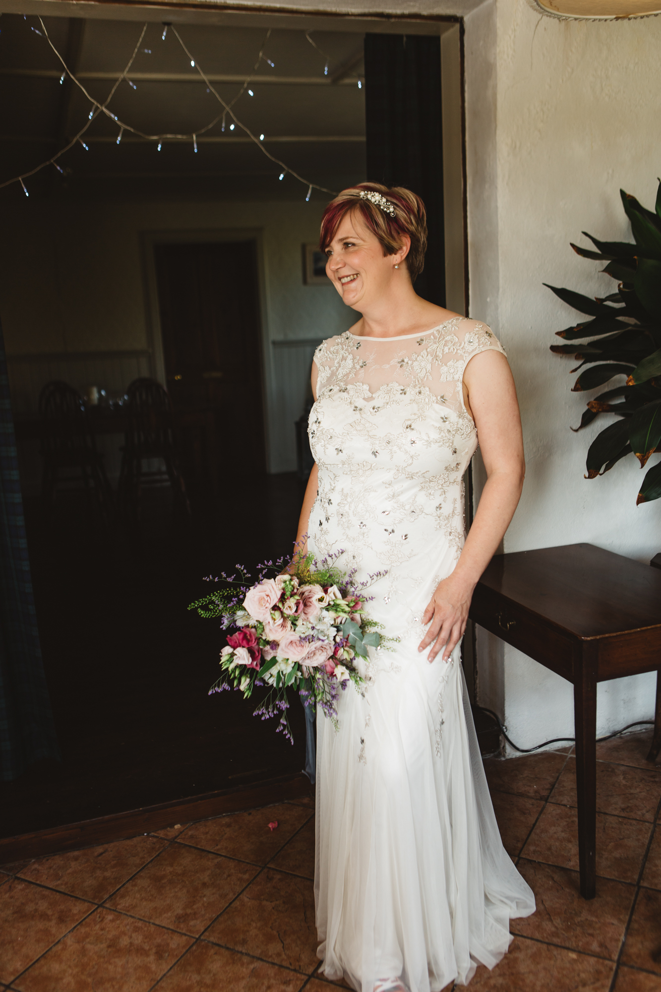 Beaming bride in wedding dress short pink hair holding bouquet