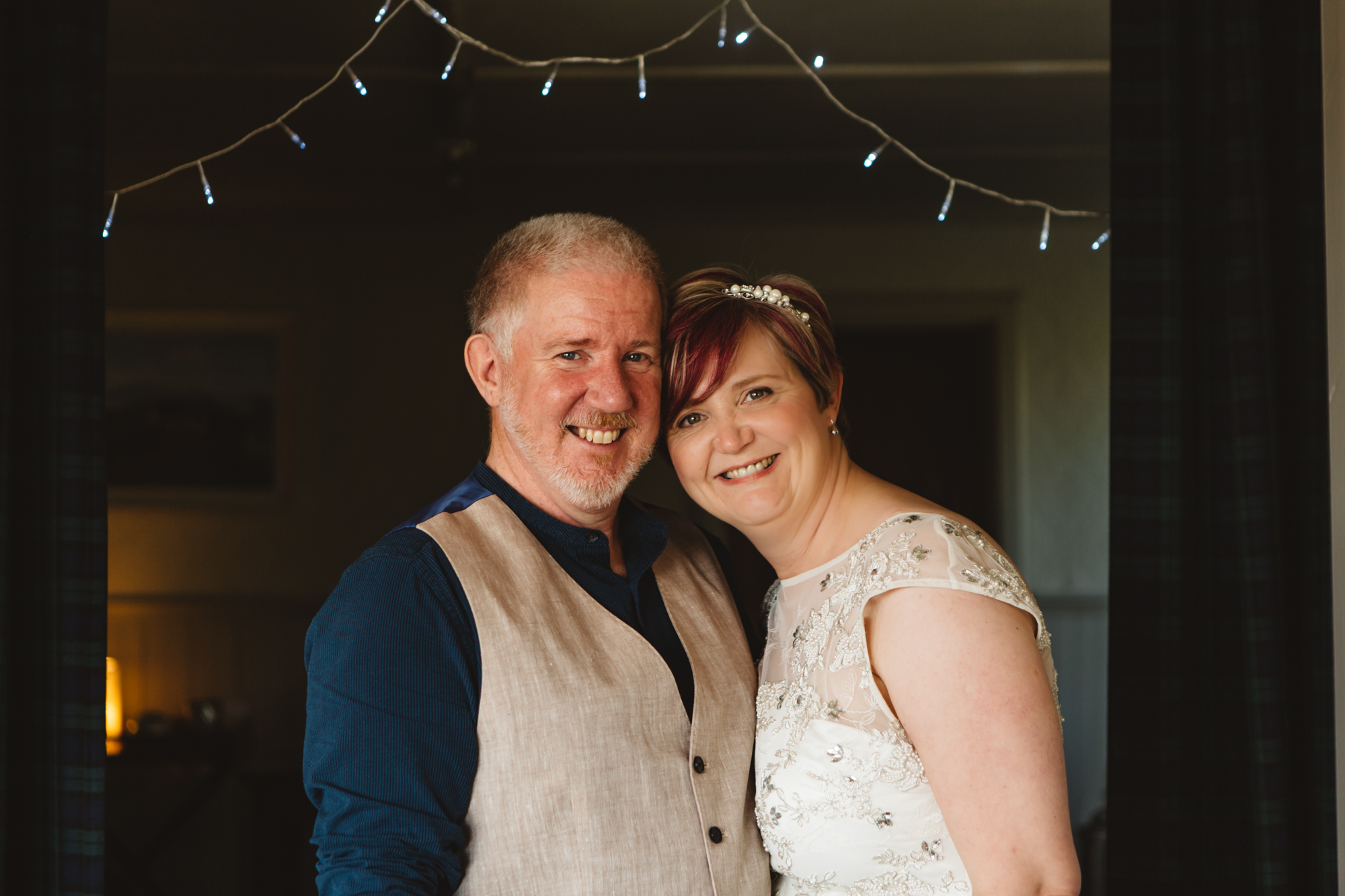 smiling bride and groom with fairy lights
