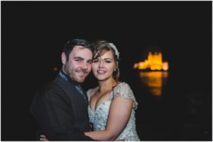 Bride and Groom at night with Eilean Donan Castle floodlight in background
