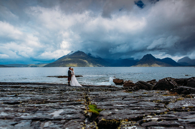 Bride and groom on rock slabs at Elgol view of Cuillins Isle of Skye