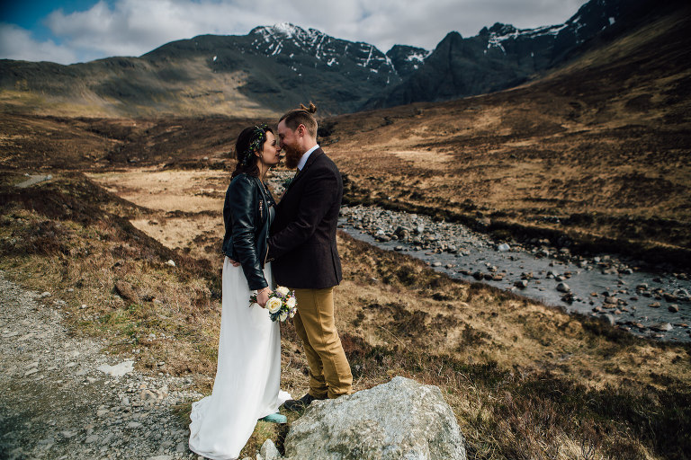 Bride and groom kiss at Fairy Pools Isle of Skye. Bride wearing leather jacket over wedding dress and floral crown