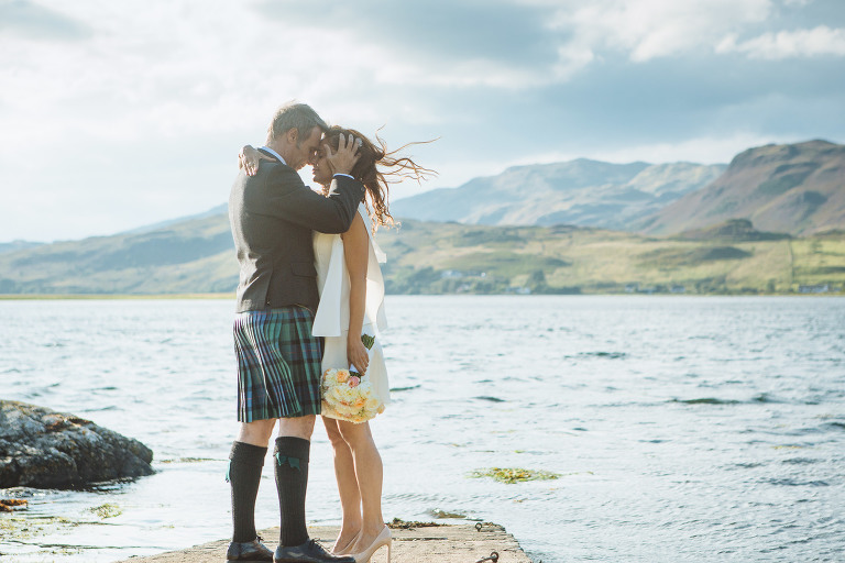 bride and groom stand on slipway at Eilean Donan Castle