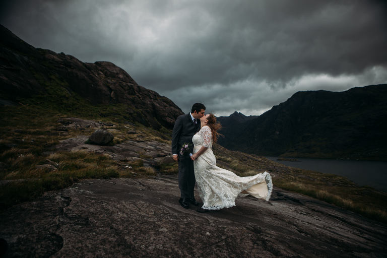 Bride and Groom kiss against stormy background Loch Coruisk Isle of Skye
