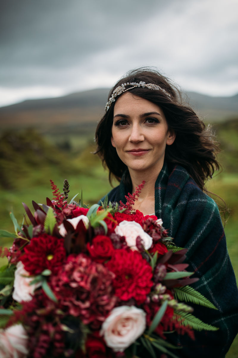 Dark haired bride with tartan wrap and rod bouquet Isle of Skye