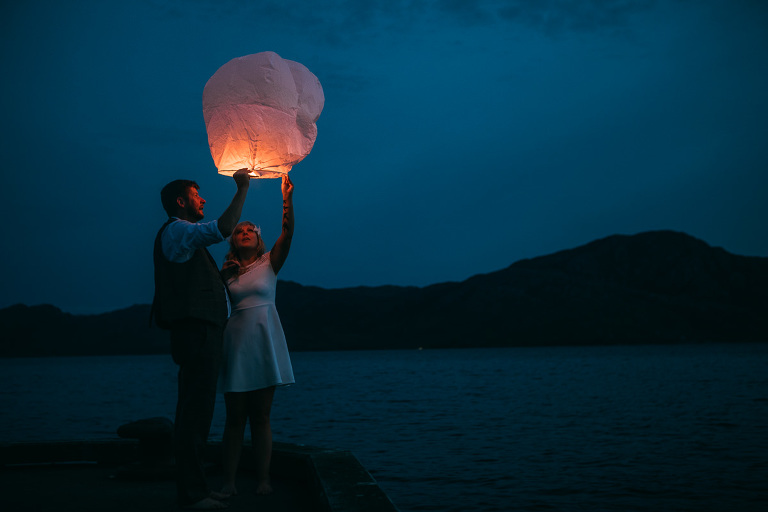 Sky lanterns at sunset Knoydart Scotland held by bride and groom