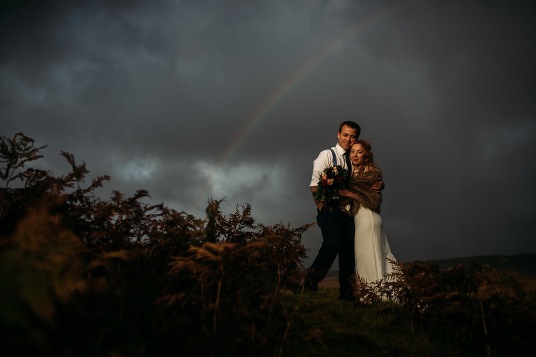 Bride and Groom embrace late afternoon light and rainbow Isle of Skye