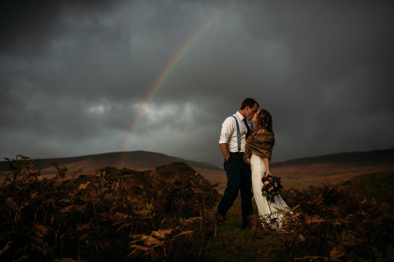 Young bride and groom kiss at Fairy Glen Isle of Skye autumn colours and rainbow in stormy sky