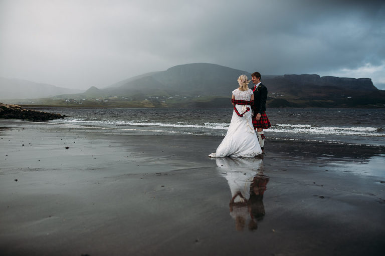 Wedding couple reflected in wet sands Staffin beach Isle of Skye Quiriaing in bakground