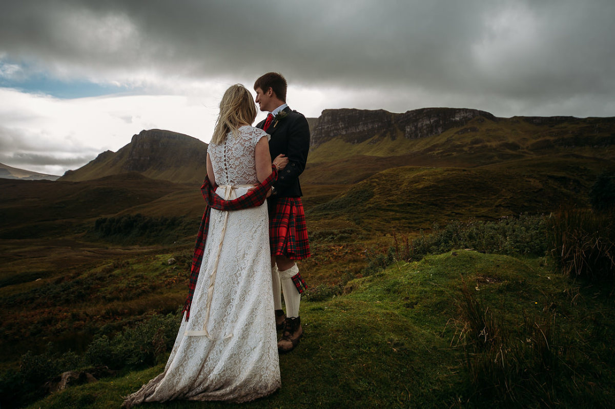 Kilted groom and bride facing to sea from Quiraing Isle of Skye wedding